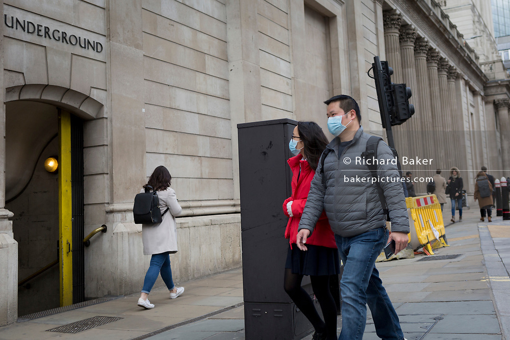 On the day that Chancellor of the Exchequer Rishi Sunak unveiled a £30bn package to boost the economy and get the country through the coronavirus outbreak, two Asians wearing a surgical masks walks past Bank Underground Station in the capital's financial district, as the Bank of England's governor Mark Carney cut the interest rate from 0.75% to 0.25%, on 11th March 2020, in the City of London, England.