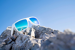 Close-up of sunglasses on rock against sky
