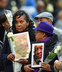 People hold photos and flowers as they leave after the Grenfell Tower National Memorial Service at St Paul's Cathedral in London, to mark the six month anniversary of the Grenfell Tower fire.