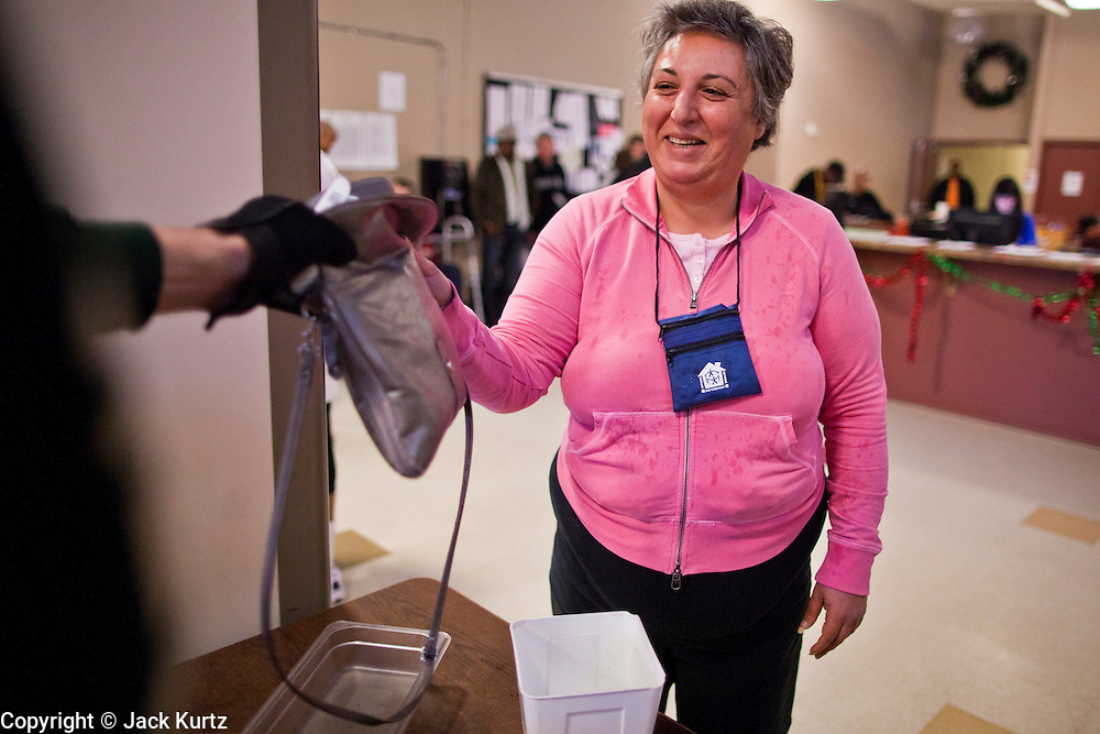 """29 DECEMBER 2010 - PHOENIX, AZ: MIRELLA, a homeless woman, goes through security while checking in for the night at Central Arizona Shelter Services (CASS) in downtown Phoenix Wednesday. Phoenix was hit by a winter storm Wednesday that brought heavy rain and unusually cold temperatures, it is the first day of what is expected to be a week of below normal temperatures. Morning lows by Friday are expected to be 15-20 degrees blow normal. Normal lows for Phoenix are in the 40's but by Friday are expected to be in the 20's. A spokesman for CASS said they expected to fill all of their regular shelter spaces and most of their overflow spaces every night for the next week. In addition to the cold weather CASS has seen demand for the services increase sixfold in the last three years as the Phoenix economy has slid into recession. Many CASS clients now are the """"new"""" homeless - people who used to have homes but lost their homes in the bad economy.      PHOTO BY JACK KURTZ"""