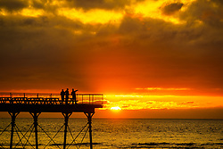 ©Licensed to London News Pictures. 16/09/2019 Aberystwyth UK. <br /> People standing on Aberystwyth's Victorian seaside pier are silhouetted as they watch the last rays of the suns as it sets over Cardigan Bay, on a glorious mid autumn evening, The week ahead is expected to be warm and settled with a high pressure system dominating the weather in the southern parts of the UK. Photo credit Keith Morris/LNP