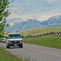 Cars drive south on Sourdough Road near Bozeman, Montana.  The Bridger Mountains rise in the background.