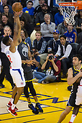 Golden State Warriors forward Andre Iguodala (9) challenges LA Clippers guard Tyrone Wallace (12) at the basket at Oracle Arena in Oakland, California, on February 22, 2018. (Stan Olszewski/Special to S.F. Examiner)