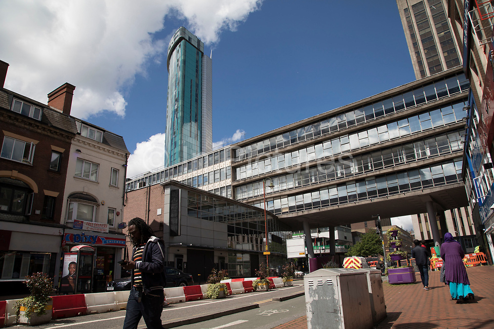 Radisson Hotel high rise tower looms large behind 1960s architecture in central Birmingham, United Kingdom.