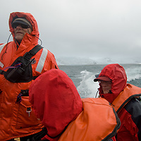 Tourists brave wind, rain and waves in a Zodiac raft en route back to their ship from Half Moon Island, Antarctica.