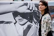 A shopper walks beneath a large billboard for a fashion retailer on Oxford Street, on 8th July 2021, in London, England.