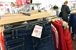 Close up of clothes in a British Red Cross charity shop UK