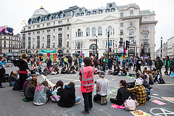 London, UK. 16th April 2019. Young climate change activists from Extinction Rebellion occupy Piccadilly Circus on the second day of International Rebellion activities to call on the British government to take urgent action to combat climate change.