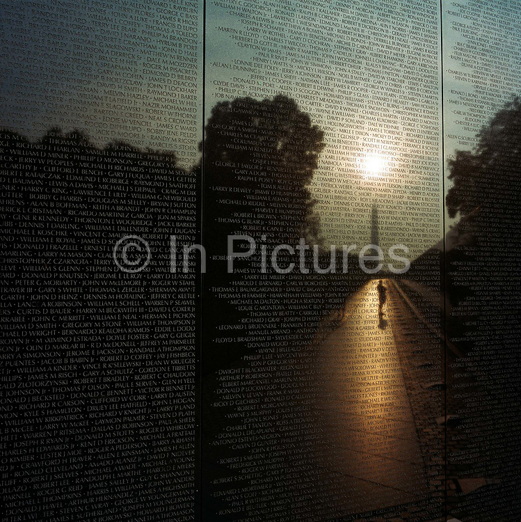 At dawn, a week after the September 11th attacks in New York and in Washington DC, we see the haunted figures of war veterans looking up at the names of dead comrades of the Vietnam Veterans Memorial in Constitution Gardens, Washington DC where 58,195 names of casualties are recorded on its polished wall. In the foreground are some of those mens' identities whose average age was 19 in the sixties and seventies. A hazy sun rises over the point of the Washington Memorial at a time when the nation was mourning those killed in the New York and Washington attacks, when the military was about to mobilise once again with many American lives lost. The Vietnam war however, remains a low-point in the nation's history and the old men who survived return to trace their buddies which helps them deal with the traumatic loss of their friends and their own youth.