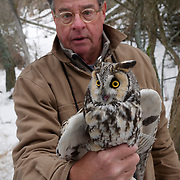 Dr. Steve Hiro of the Owl Research Institute gently holds a long-eared owl captured for study and soon to be released. Missoula, Montana