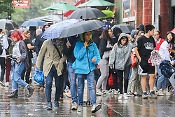 © Licensed to London News Pictures. 30/07/2019. London, UK. People shelter from the rain beneath umbrellas in Camden Market, north London during heavy rainfall. Photo credit: Dinendra Haria/LNP