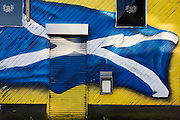 A sprayed Cross of St Andrew flag of Scotland flies across the wall and shutter of a closed bar in south Glasgow's Goven Hill.