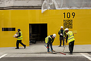 Workemen in high viz jackets sweep up outside a shop under renovation which is surrounded by a bright yelow hoarding on Bond Street on 25th May 2021 in London, United Kingdom. These high end brands are seen next to each other on a very ordinary wall. Bond Street is one of the principal streets in the West End shopping district and is very upmarket. It has been a fashionable shopping street since the 18th century. The rich and wealthy shop here mostly for high end fashion and jewellery.
