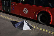 A discarded broken umbrella and side of a bus in Charing Cross Road, central London.