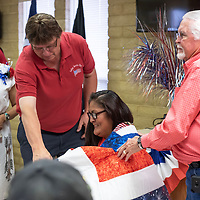 Melanie Metzler, sitting, smiles as she is presented her quilt from John Matajcich, left, and Mayor Jackie Mckinney, right at the Veterans Helping Veterans building in Gallup Friday.