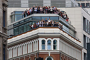 "London, 10th September 2012. Office workers watch the Olympic parade from their City balcony as thousands of spectators lined the capital's streets to honour 800 of TeamGB's athletes and Paralympians. Britain's golden generation of athletes in turn said thank you to its Olympic followers, paying tribute to London and a wider Britain as up to a million people lined the streets to celebrate the ""greatest ever"" sporting summer and billed to be the biggest sporting celebration ever seen in the UK."