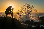 Photographer shooting spray from breaking waves at Thor's Well at sunset, Cape Perpetua Scenic Area, Siuslaw National Forest, Oregon Coast, Oregon