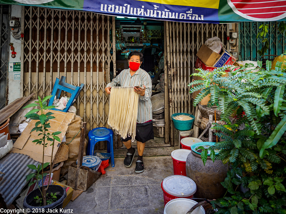 """29 DECEMBER 2018 - BANGKOK, THAILAND: A woman carries longevity noodles out of the shophouse to drying racks in front of her home. The family has been making traditional """"mee sua"""" noodles, also called """"longevity noodles"""" for three generations in their home in central Bangkok. They use a recipe brought to Thailand from China. Longevity noodles are thought to contribute to a long and healthy life and  are served on special occasions, especially Chinese New Year, which is February 4, 2019. These noodles were being made for Chinese New Year.        PHOTO BY JACK KURTZ"""