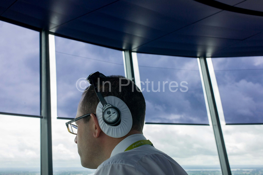 NATS Heathrow air traffic controller in control tower at Heathrow airport, London. The back of the head of the controller is seen as he looks out of the panoramic window. Controlling aviation traffic on the ground and in the controlled airspace around London, the NATS controllers help safely guide up to 6,000 flights a day from the top of the 87 metre high tower, handling 1,350 aircraft movements a day into Heathrow.