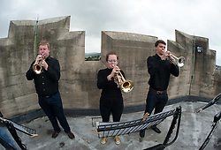 "© Licensed to London News Pictures. 27/07/2015. Bristol, UK.  ""Fanfare for Bristol"", titled ""At the Top of the Tide"", composed by David Mitcham, commissioned by Bristol Proms 2015.  Picture shows trumpeters l-r: Chris Hart, Helen Whitemore, Gideon Brooks, playing at the top of the Wills Memorial Bell Tower.  The fanfare was performed live for the Mayor of Bristol, George Ferguson and Artistic Director of the Bristol Old Vic, Tom Morris for the first time at Bristol's famous Temple Mead train station, heralding the opening of the Bristol Proms 2015.  David Mitcham's  ""At the Top of the Tide"" was inspired by 'Bristol's inextricable links to the sea'.  The first performance by Arc Brass took place outside the Engine Shed, and throughout the day, performances took place at the Watershed, Pero's Bridge, the Wills Memorial Bell Tower and finally at Bristol Old Vic itself. David Mitcham, who has worked extensively for the BBC Natural History Unit based in Bristol said: ""I am thrilled that my Fanfare ""At the Top of the Tide"" has been chosen for the city of Bristol and to open Bristol Proms 2015. I hope the Fanfare represents the rich diversity of Bristol, its maritime and industrial heritage as well as being a celebration of the spirit of the city and the energy it will carry into the future.""  Bristol Proms 2015 runs from today, 27th July to 1st August and features some of the world's finest musicians including Alison Balsom, Miloš Karadaglić, Pumeza Matshikiza and Daniel Hope.  Photo credit : Simon Chapman/LNP"