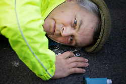 © Licensed to London News Pictures. 25/10/2021. London, UK. An Insulate Britain climate change activist with his head glued to the road in an attempt to bloc traffic on Bishopsgate in the City of London. The group have restarted their actions to block motorways and major roads causing disruption in the week before the COP26 climate meeting in Glasgow on 31/10/2021. Photo credit: Ben Cawthra/LNP