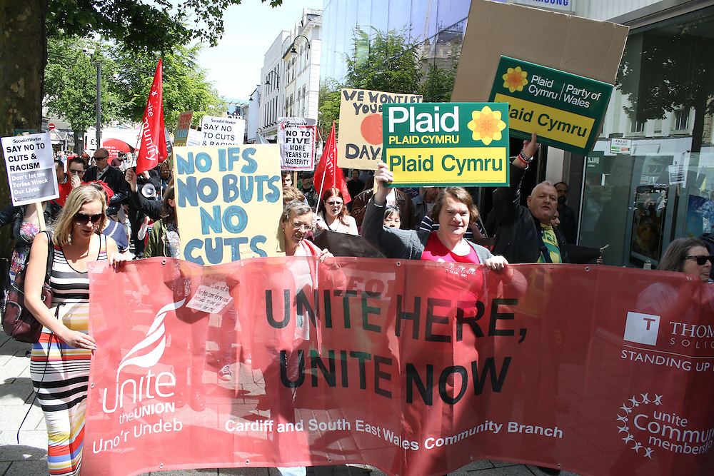 Protesters march down Queen Street, Cardiff, in opposition to government cuts to public services