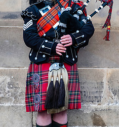 Scottish man wearing traditional tartan and kilt playing bagpipes on Royal Mile in Edinburgh Old Town , Scotland, United kingdom
