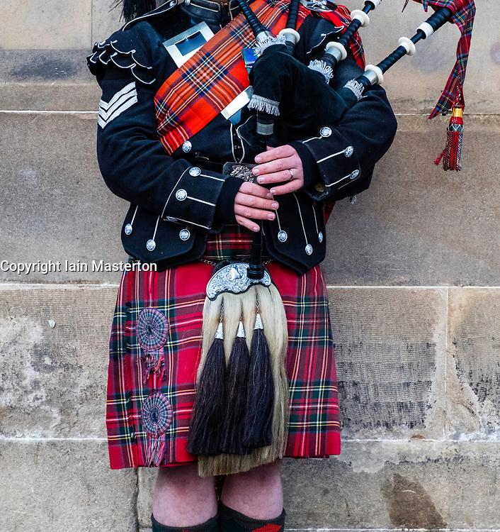 Scottish man wearing traditional tartan and kilt playing bagpipes on Royal Mile in Edinburgh Old Town , Scotland, United kingdom