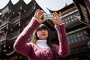 Young woman takes photograph on zigzag bridge at Yu Gardens Bazaar Market, Shanghai, China