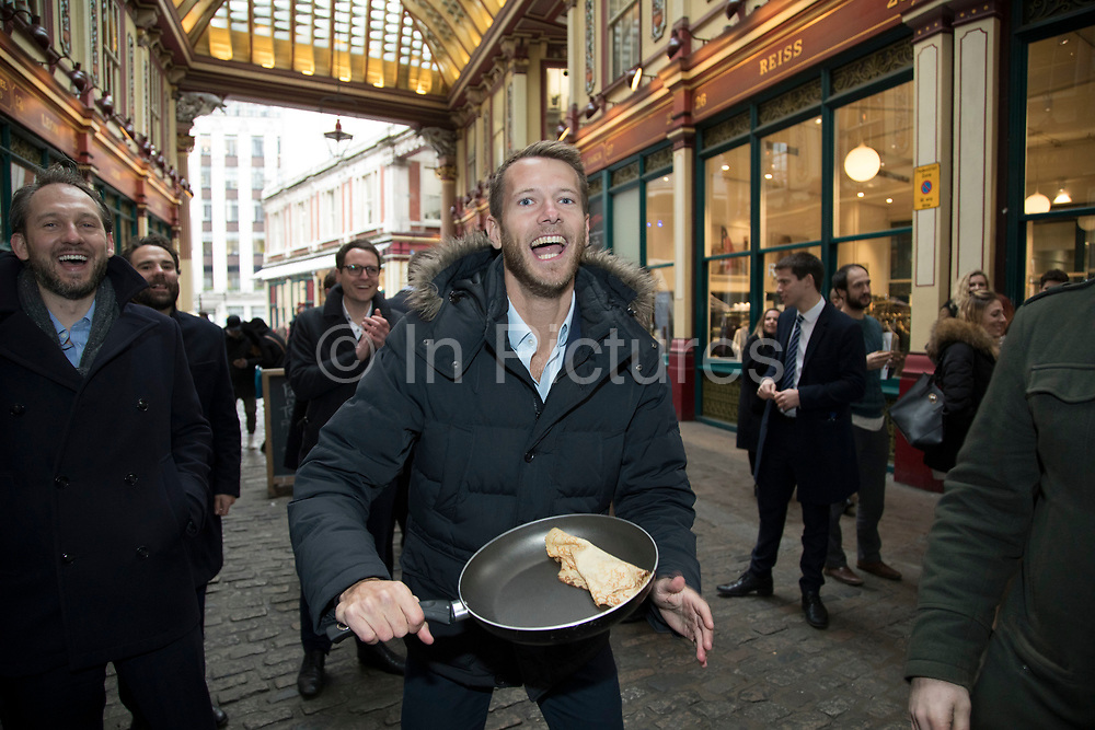 Shrove Tuesday festivities as The City Flippers, celebrate winning the Leadenhall Market Pancake Day Race on 13th February 2018 in London, United Kingdom. Competing teams of City workers outside The Lamb Tavern tackle the 25m course, competing to win the coveted frying pan trophy as they flip their wayaround the historic 14th century market.