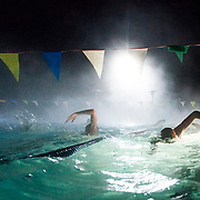 Students swim in an open pool in Huntersville, NC during SwimMAC practice.