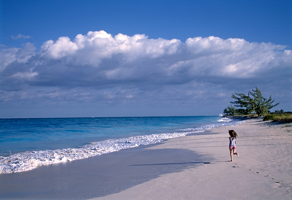 Rear view of young girl running away on Grace Bay beach
