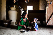 Pramila Tharu, 15, comforts her 2 year old toddler Prapti, in Bhaishahi village, Bardia, Western Nepal, on 29th June 2012. Pramila eloped and married at 12 and gave birth to Prapti at age 13. She delivered prematurely on the way to the hospital in an ox cart and her baby weighed only 1.5kg at birth. In Bardia, StC works with the district health office to build the capacity of female community health workers who are on the frontline of health service provision like ante-natal and post-natal care, especially in rural areas. Photo by Suzanne Lee for Save The Children UK