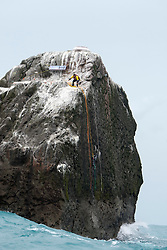 Nick Hancock (yellow) climbs up to the top of Rockall with his Help for Heroes flag, for his reconnaissance mission for a future 60 day occupation of Rockall. The Rockall Jubilee Expedition, a unique endurance expedition to be undertaken by Nick, in order to raise funds for Help for Heroes .©Michael Schofield..