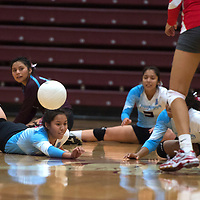 Ganado Hornet Tiara Cook (2) dives under the ball keeping it in play during the Tuesday game in Ganado against Monument Valley.