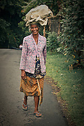 An older Balinese woman carries a bag on top of her head. It is often the preferred way, especially by women.