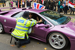 Whitehall, London, November 5th 2015. UK Egyptians demonstrate in support of President Abdel Fatah al-Sisi as supporters of ousted Mohamed Morsi and human rights groups protest outside Downing Street as the leader visits Prime Minister David Cameron at No. 10.  PICTURED: A Police officer lectures a lamborghini driver who had been loudly revving his engine supporters of President Sisi.
