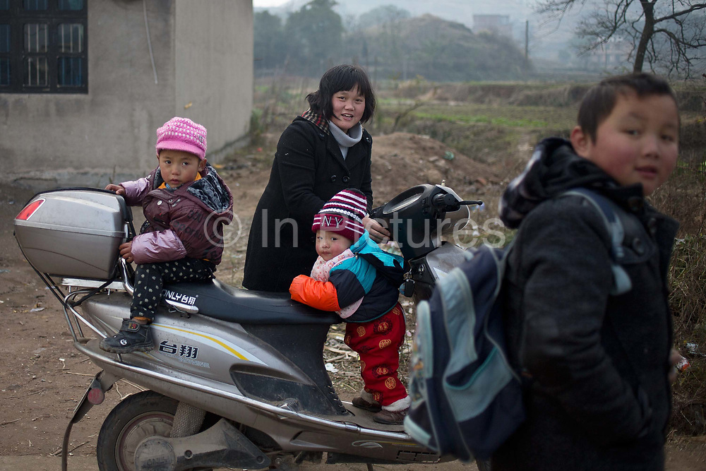 Two young brothers, aged four and one- and-half , climb on a scooter while their oldest 8 year old brother walks toward school at a rural village in Shangrao, Jiangxi Province, China on 12 December 2012.   The villages near the city of Shangrao are known for openly defying China's one child policy as most families have more than one child.