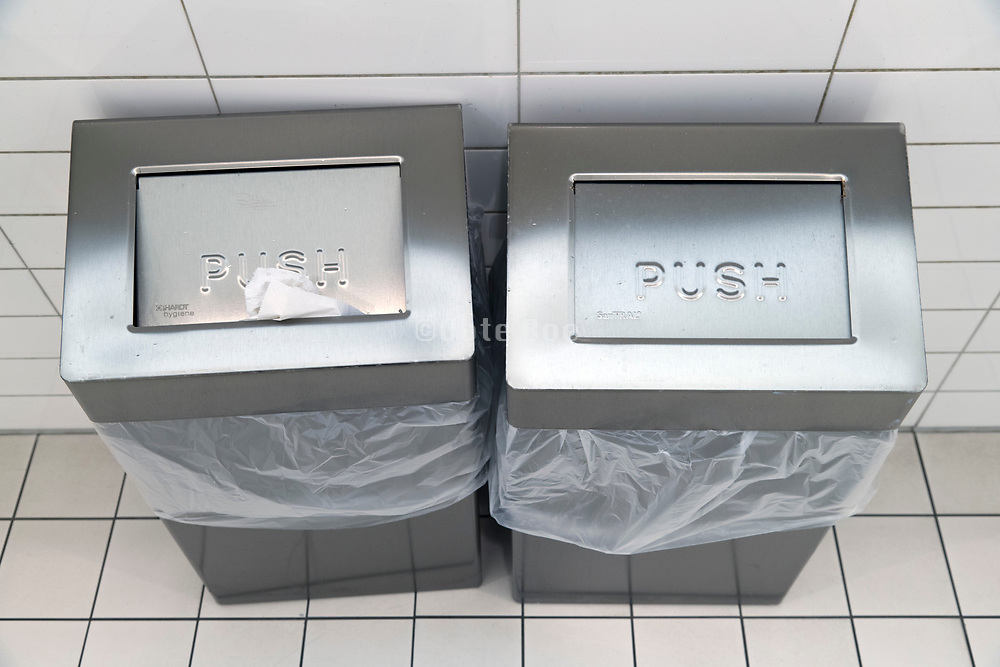 paper towel waste baskets in a public restroom