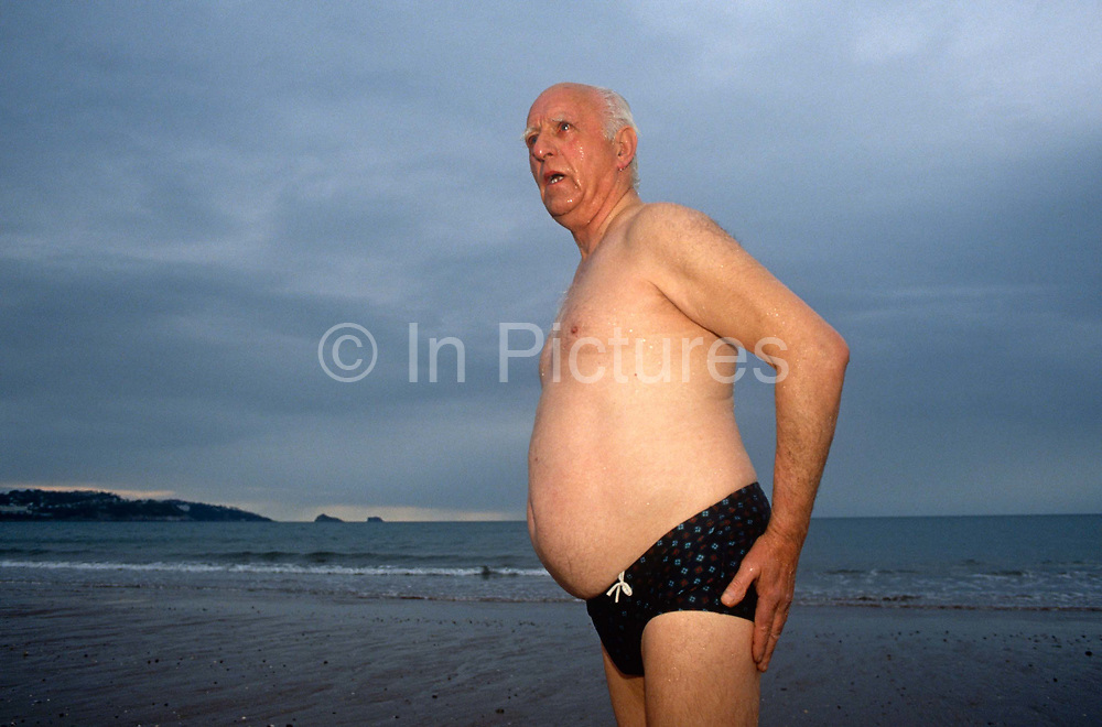 An elderly gentleman has just emerged from a swim in the cold waters off Paignton, the seaside town in Devon, south-west England. Still to towel himself down, he looks chilled to the bone but stands talking to friends out of view. The man wears dark trunks (costume) and has a large belly but otherwise looks fit and healthy, a true picture of health for a man of his age, after swimming in these seas for many years and enjoying the endorphins that are stimulated after wild, outdoor swims.
