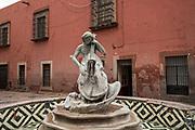 Water fountain musician playing the cello behind the San Francisco Church in the old colonial section of Santiago de Queretaro, Queretaro State, Mexico.
