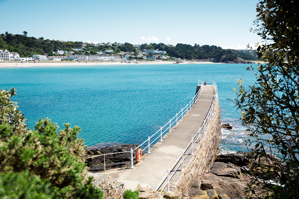 View down the pier and across the sea towards the beachfront hotels and tourist accommodation at the beach in St Brelade's Jersey, Channel Islands