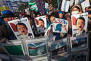 Protestors carry images of Prime Minster Abe with a Hitler moustache at a rally to protest the construction of a new US military base at Henoko in Okinawa outside the Japanese National Diet building, Nagatacho, Tokyo, Japan Sunday January 25th 2015. Organisers say 7,000 people joined the protest and formed a human chain around the Assembly building.