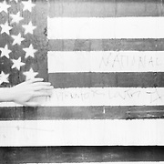 outstretched hand touching american flag painted wall with word nationalism on flag