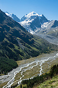 """The icy Bernina Range rises above Ova da Roseg river valley, near Pontresina, Switzerland, in the Bernina Alps, Europe. Tschierva Glacier flows from Piz Roseg (3937 m). Val Roseg is in the Swiss canton of Graubünden (or Grisons / Grigioni / Grischun); the lower Roseg Valley is in Pontresina, whereas the upper valley is in an exclave of Samedan Municipality. Hike from Pontresina up Roseg Valley to Fuorcla Surlej for stunning views of Piz Bernina and Piz Roseg, finishing at Corvatsch Mittelstation Murtel cable car. Walking 14 km, we went up 1100 meters and down 150 m. Optionally shorten the hike to an easy 4 km via round trip lift. The Swiss valley of Engadine translates as the """"garden of the En (or Inn) River"""" (Engadin in German, Engiadina in Romansh, Engadina in Italian), and is part of the Danube basin."""