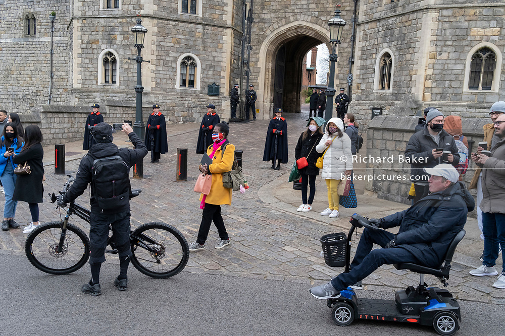 The day after the death at age 99 of Prince Phillip, the Duke of Edinburgh, consort to Queen Elizabeth II, the public pass-by armed police officers and women members of the Royal Household stand outside Windsor Castle where the Queen has been isolating throughout the Coronavirus pandemic, on 10th April 2021, in London, England.