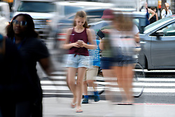 Pedestrians engaged in cell phone activity and rush hour traffic reflected in the windows of an office building in Center City Philadelphia, PA, on July 26, 2018.