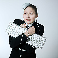 studio shot portrait of a beautiful young woman in a costume suit attached to a computer keyboard and been attack by a mouse