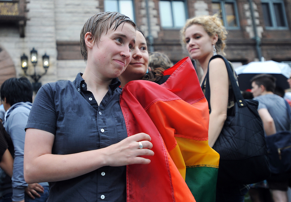 Otto (left) and Laura O'Connor take shelter from the rain under a multicolored flag during a July Supreme Court Marriage Equality Decision Rally at Cambridge City Hall.