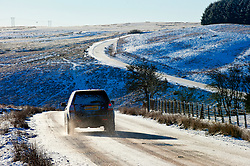 © Licensed to London News Pictures. 18/01/2015. A motorist drives through a wintry lanscape 400 metres above seal level on the high moorland of the Mynydd Epynt. Mid Wales woke to sub zero temperatures and a beautiful blue sky. Mynydd Epynt, Powys , Wales, UK. Photo credit: Graham M. Lawrence/LNP